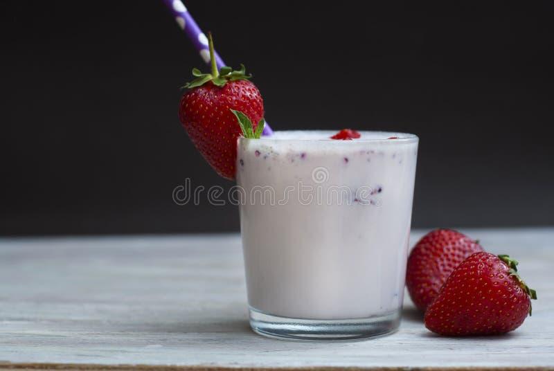 牛奶鸡尾酒与Srawberry的震动饮料 与秸杆的自创果子奶昔在玻璃 土气灰色木背景 免版税库存图片