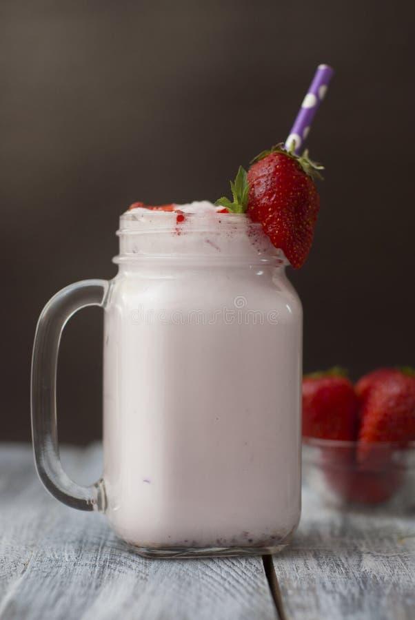 牛奶鸡尾酒与Srawberry的震动饮料 与秸杆的自创果子奶昔在玻璃 土气灰色木背景 库存图片