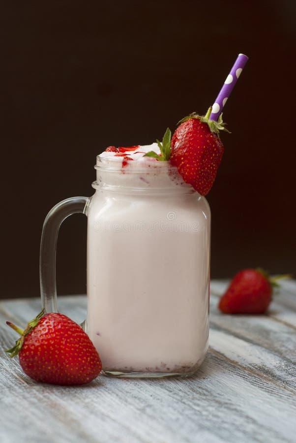 牛奶鸡尾酒与Srawberry的震动饮料 与秸杆的自创果子奶昔在玻璃 土气灰色木背景 免版税库存照片