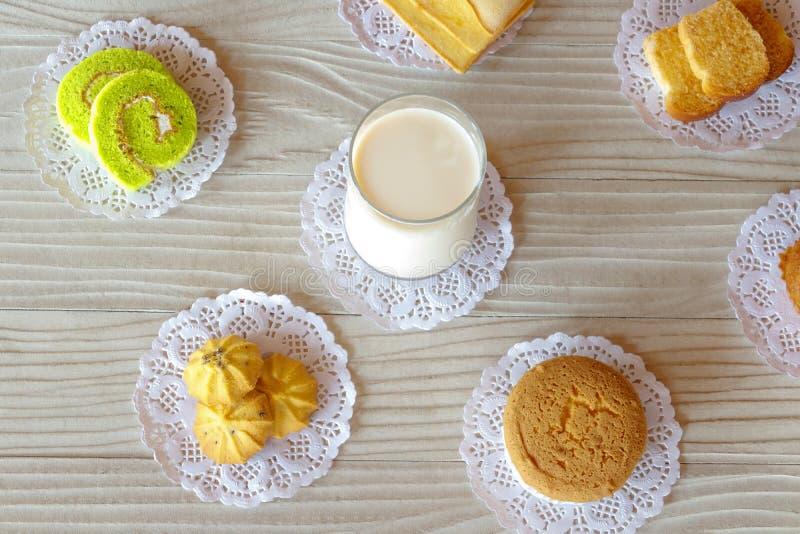 牛奶黄油面包蛋糕卷曲奇饼和杯形蛋糕蒜味面包在白色木表上 免版税库存图片