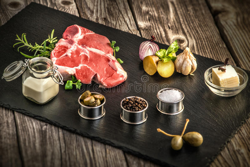 牛排、新鲜的肉oo石头板材、美食术、大蒜和葱,香料,迷迭香用肉,黄油,木桌,添加剂, preparat 库存图片