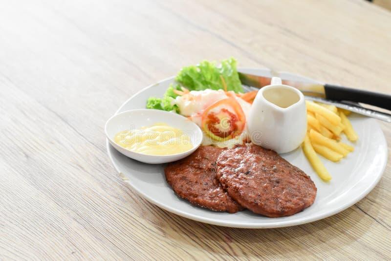 牛排、沙拉和薯条在葡萄酒木头背景 免版税库存图片