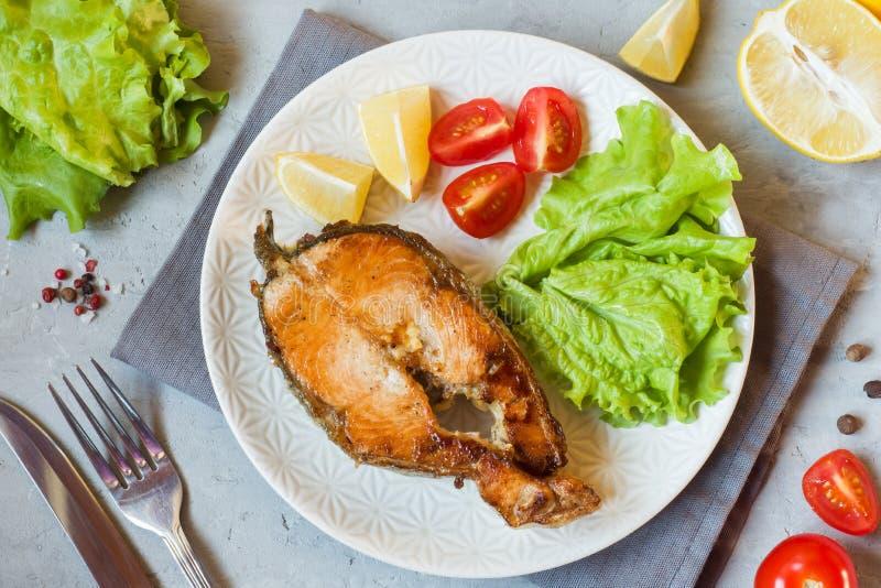 牛排在一块板材的被烘烤的三文鱼鱼有新鲜蔬菜的 库存照片
