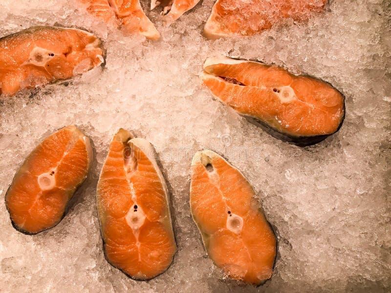 牛排大片断从红色水多的可口变冷的结冰的新鲜的鳟鱼鱼的在背景小冷的清楚的冰 库存图片
