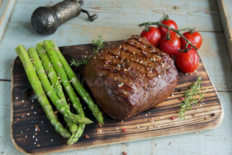 牛排烤了用芦笋木表面上的蕃茄香料 免版税库存照片