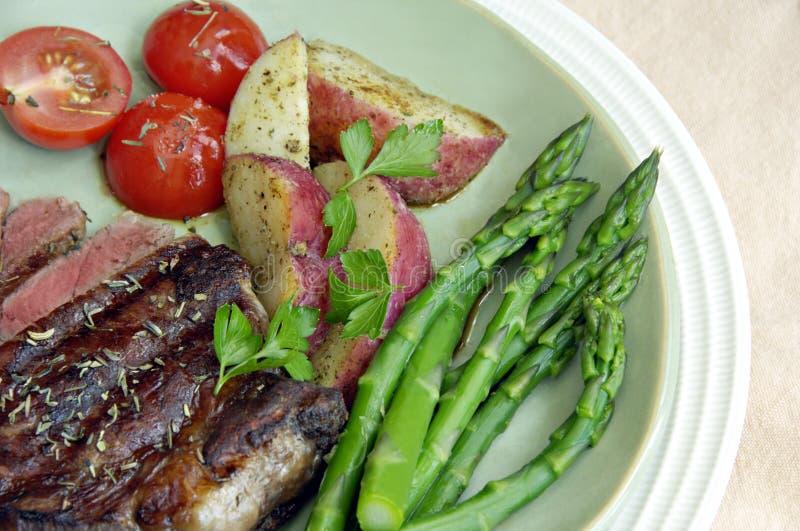 牛排用土豆、蕃茄和芦笋 图库摄影