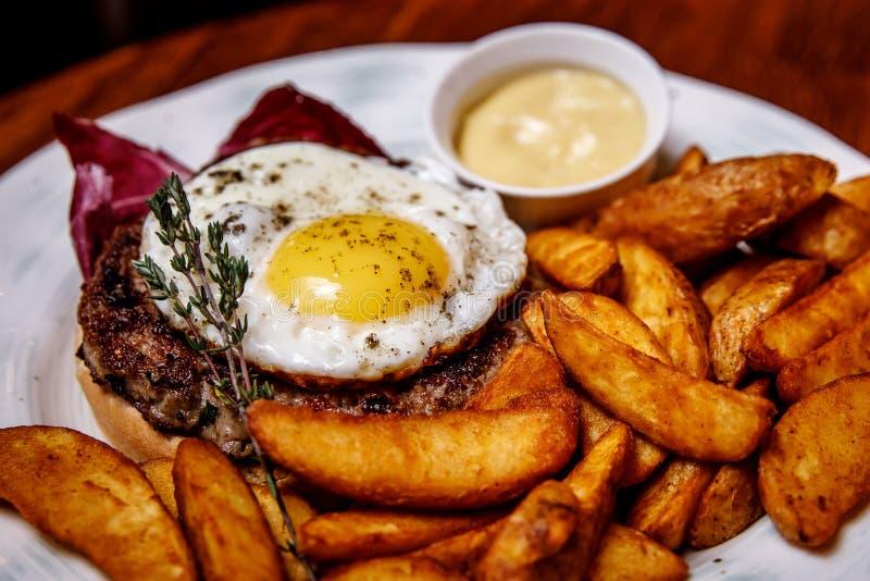 牛排用炒蛋和油煎的土豆 侧视图 服务为咖啡馆, 图库摄影