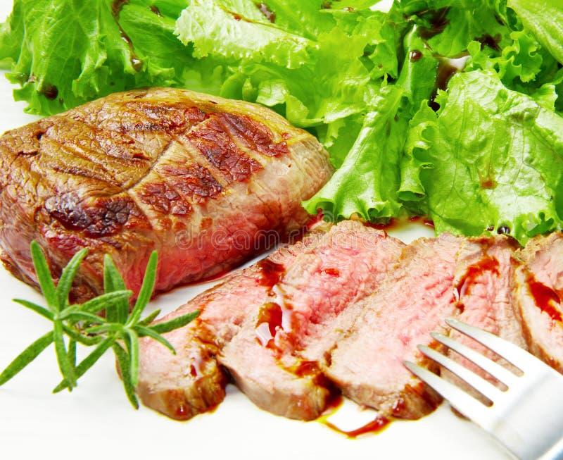 牛排肉烤用迷迭香和莴苣 免版税库存图片