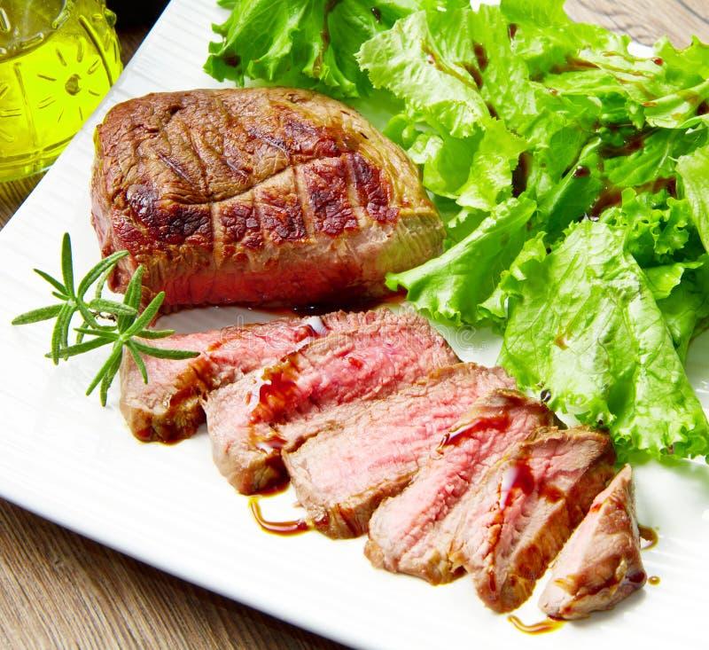 牛排肉烤用迷迭香和莴苣 库存图片