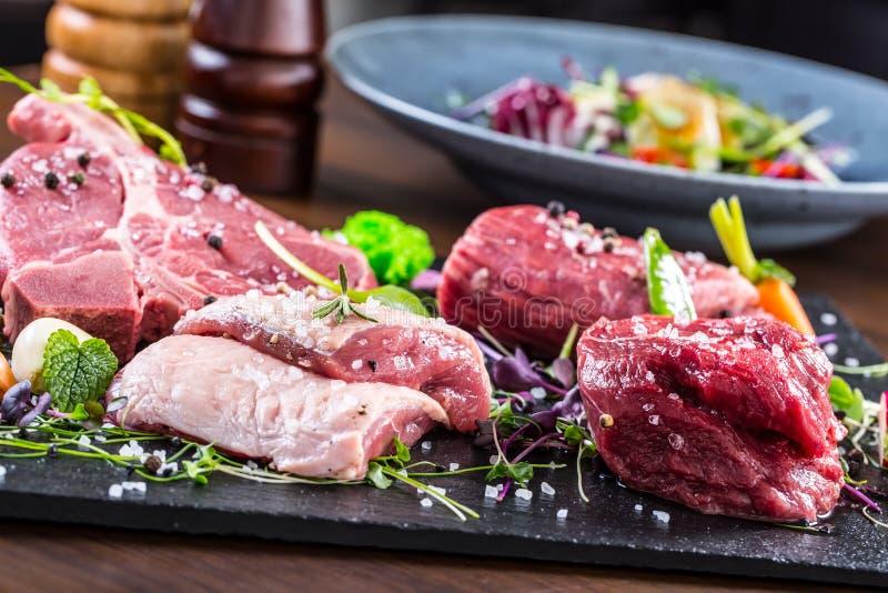牛排 牛排 肉 被分配的肉 原始的鲜肉 牛腰肉排 丁骨牛排 牛后腹肉排 鸭胸脯菜装饰 库存照片