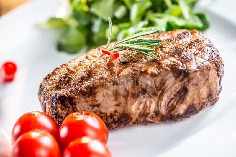 牛排 牛肉水多的牛排 与菜和杯的食家牛排在木桌上的玫瑰酒红色 库存照片