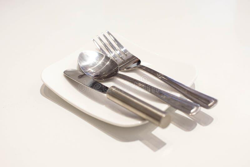 牛油刀、叉子和匙子在一块白色板材 库存图片