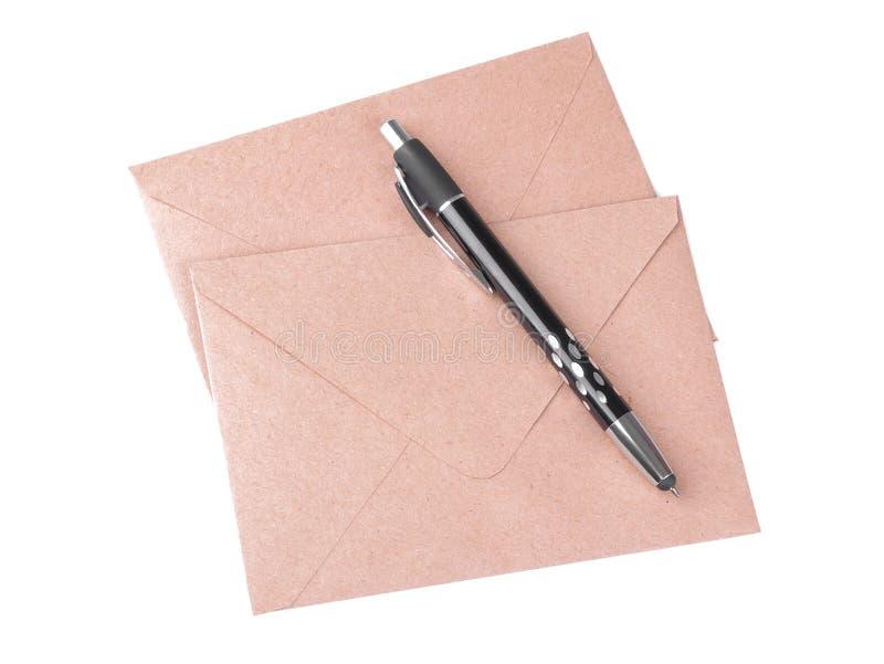 牛皮纸信封和一支笔在白色隔绝了背景 概念有信函邮件符号 免版税库存图片
