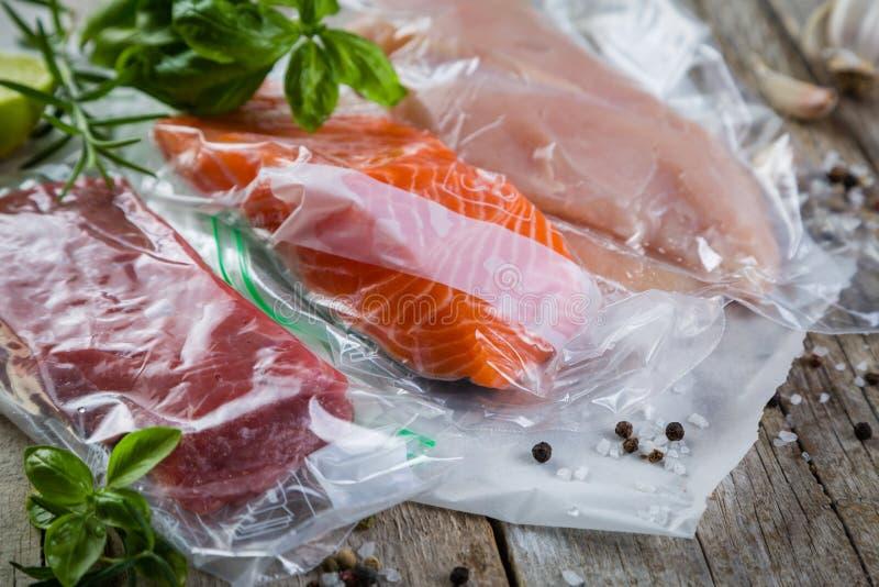 牛肉、鸡和三文鱼在真空塑料袋sous vide烹调的 库存图片