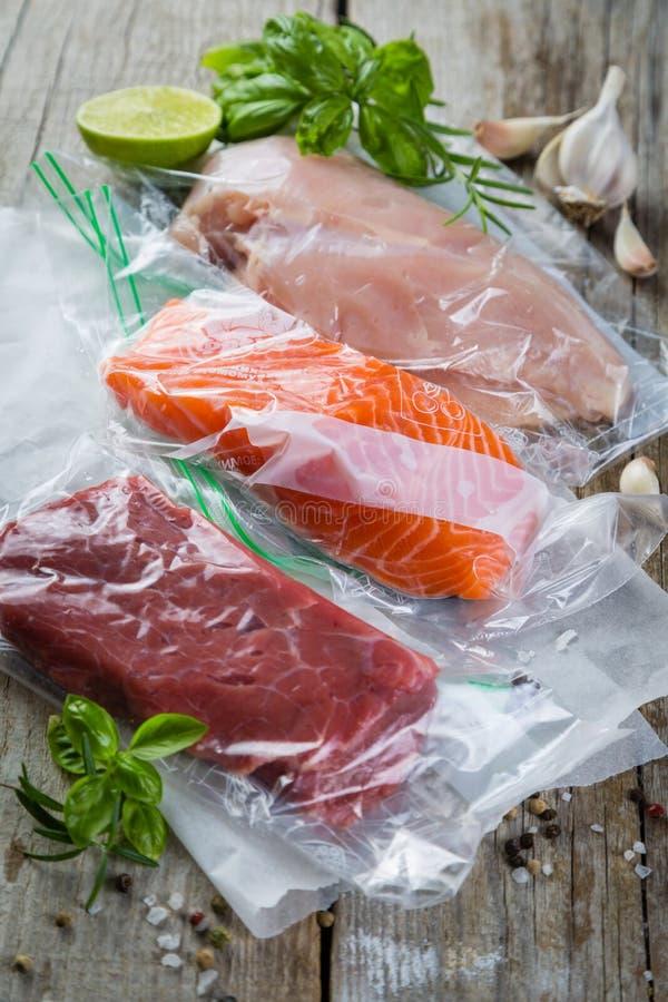 牛肉、鸡和三文鱼在真空塑料袋sous vide烹调的 库存照片