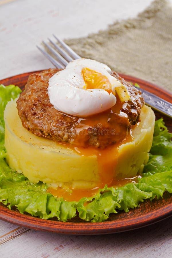 牛肉和猪肉小馅饼用荷包蛋、捣毁的土豆和莴苣 免版税库存照片