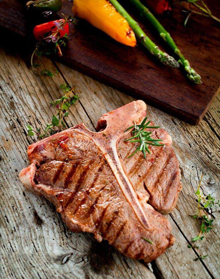 牛肉在黑暗的老木板的丁骨牛排 免版税库存图片