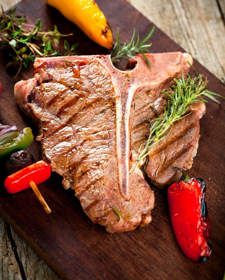 牛肉在黑暗的老木板的丁骨牛排 库存照片