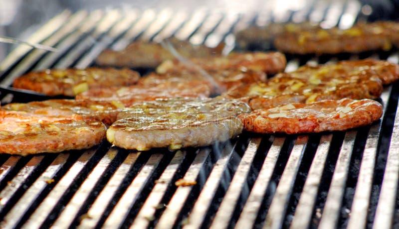 牛肉或猪肉用chehese烤肉汉堡准备的汉堡包的在bbq火火焰格栅烤了 图库摄影
