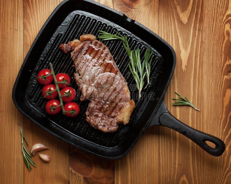 牛腰肉排用迷迭香和西红柿在煎锅 库存图片