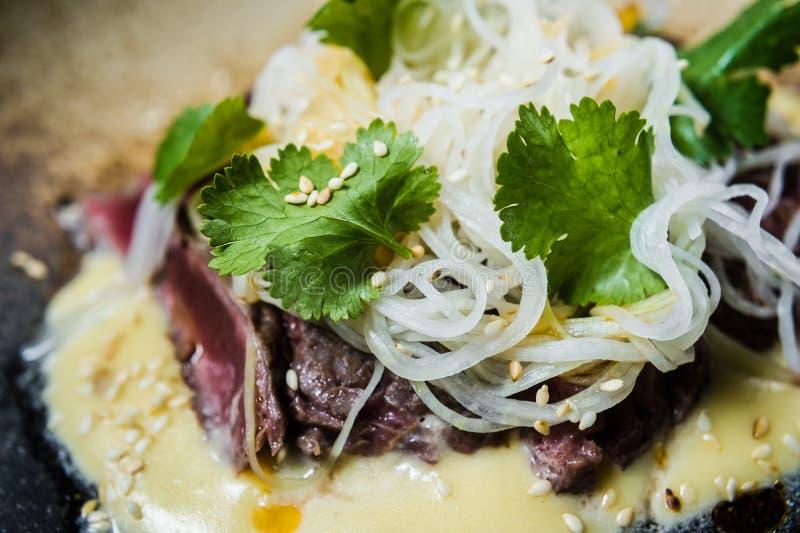 牛里脊肉用调味汁和玻璃面条,黑暗的背景 免版税库存照片
