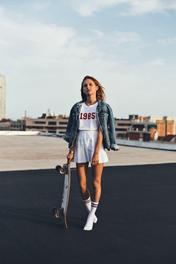 牛仔布夹克的美丽的金发碧眼的女人有滑板的 免版税图库摄影