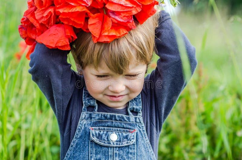 牛仔布礼服的小迷人的女孩婴孩走在与鸦片的领域的到在他的顶头花束的穿戴,红色鸦片花圈,要 库存照片