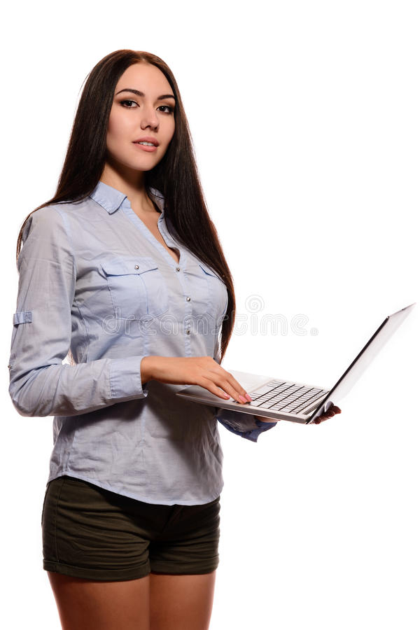 牛仔布衬衣的微笑的东方女孩是被打开的膝上型计算机 免版税库存照片