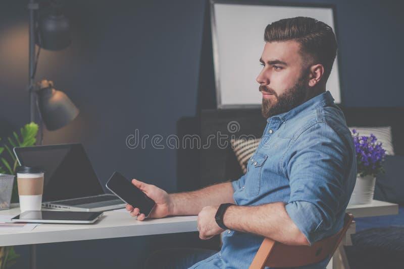牛仔布衬衣的年轻有胡子的自由职业者人在他手和认为上在家坐在桌上,拿着手机 免版税库存图片