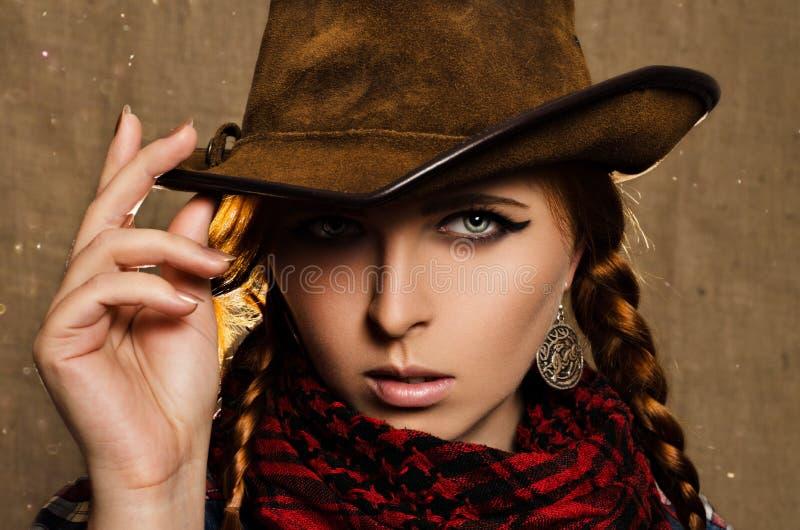 牛仔帽的美丽的年轻红发女孩 免版税库存照片
