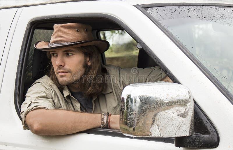 牛仔帽的英俊的人在汽车4x4 徒步旅行队样式 库存图片