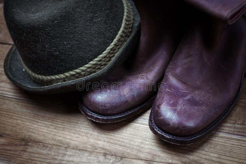 牛仔肮脏和使用的棕色靴子和帽子 免版税库存图片
