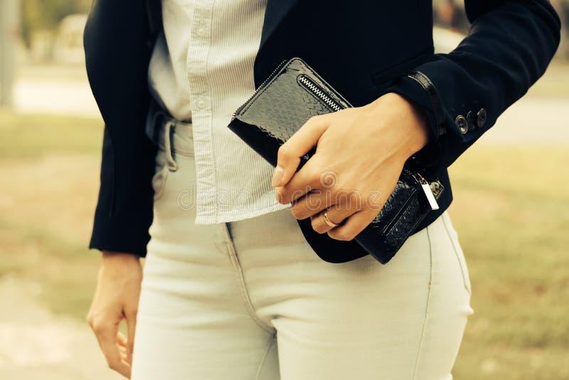 牛仔裤、衬衣和拿着在她的一件黑夹克的妇女一个钱包 库存图片