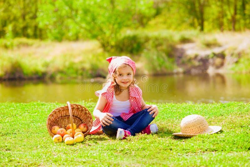 牛仔裤和一件衬衣的小女孩在一条河附近用苹果 免版税库存照片