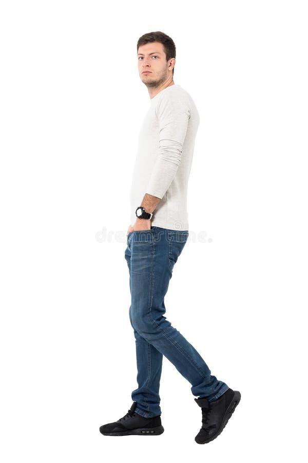 牛仔裤和浅灰色的衬衣的走和看照相机的偶然人侧视图  图库摄影