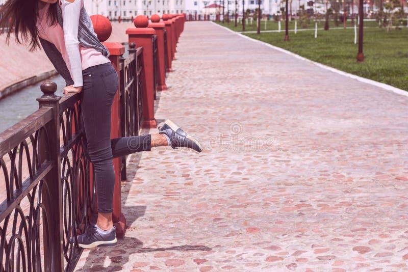 牛仔裤和运动鞋的女孩炫耀鞋子走在路的 免版税图库摄影