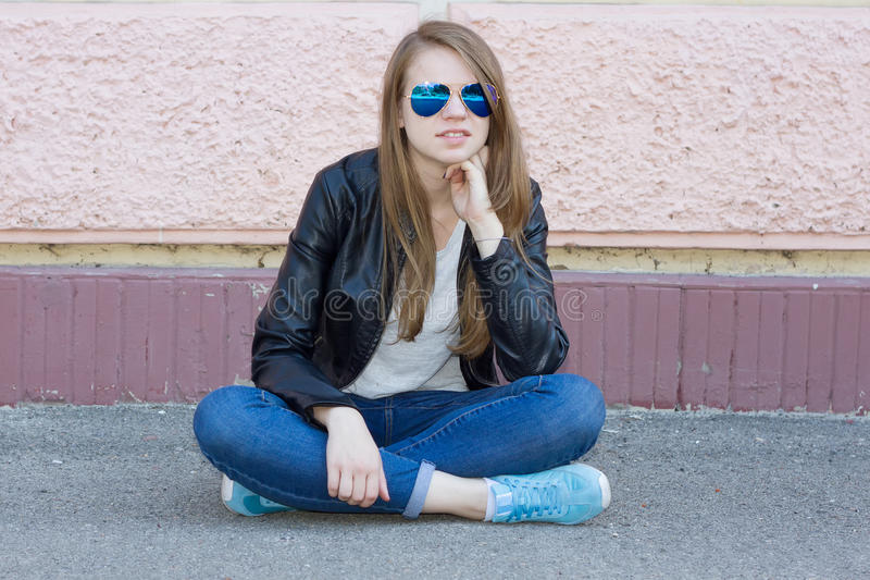 牛仔裤的女孩坐地面 免版税库存照片