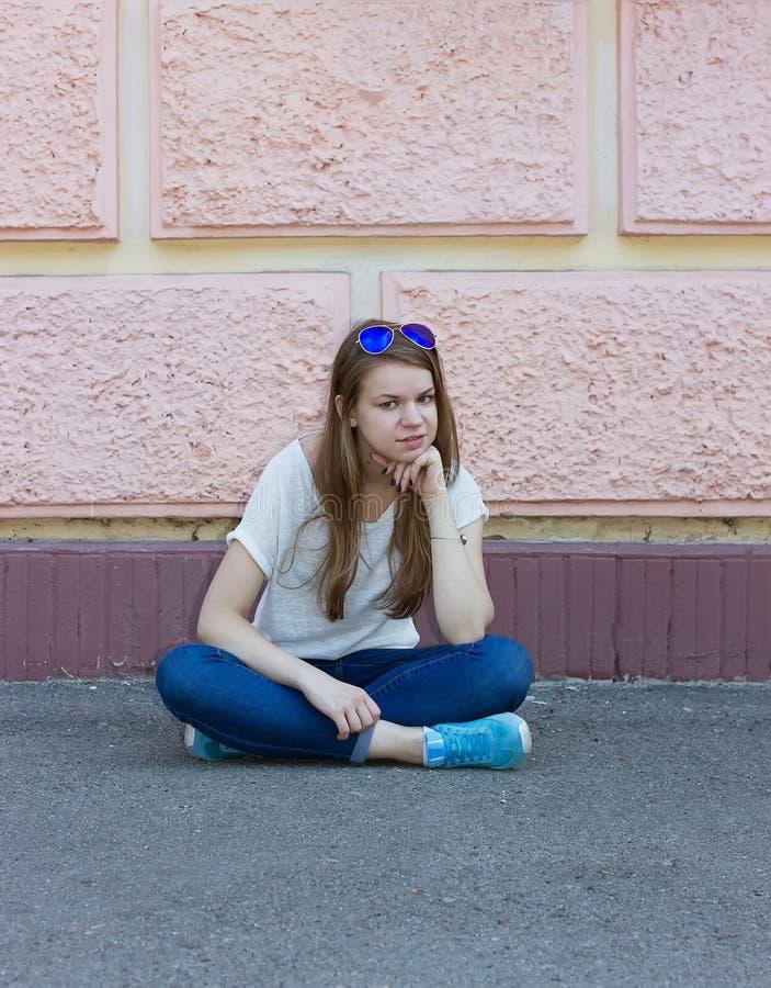 牛仔裤的女孩坐地面 库存照片