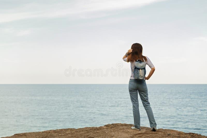 牛仔裤的少妇,在镶边上面和运动鞋在海滩b 免版税图库摄影