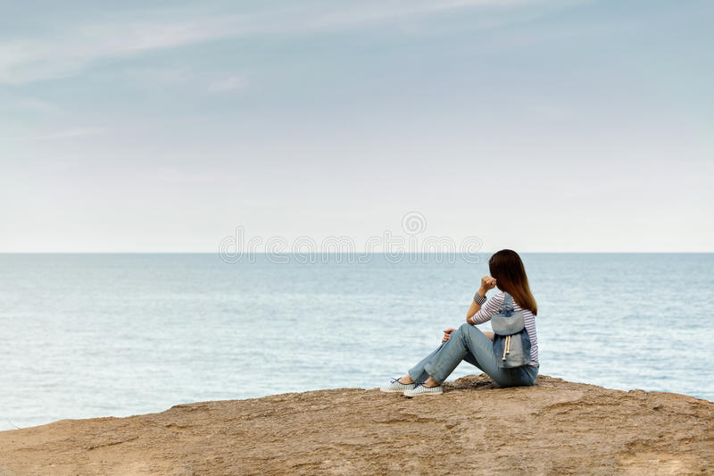 牛仔裤的少妇,在镶边上面和运动鞋在海滩b 库存图片