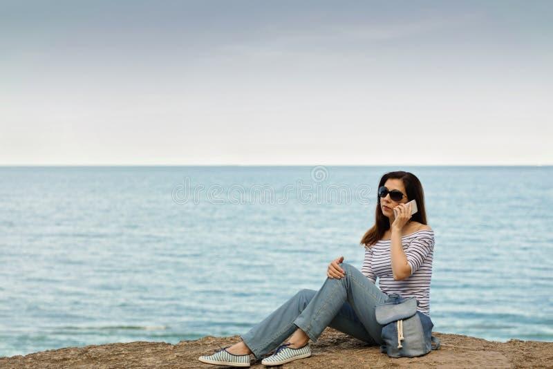 牛仔裤的少妇,在镶边上面和运动鞋在海滩b 免版税库存图片