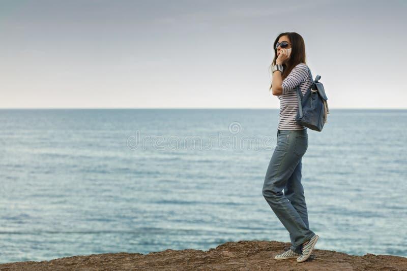 牛仔裤的少妇,在镶边上面和运动鞋在海滩b 免版税库存照片