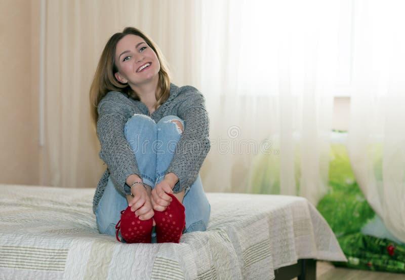 牛仔裤的愉快的妇女称呼衣物坐沙发 免版税图库摄影