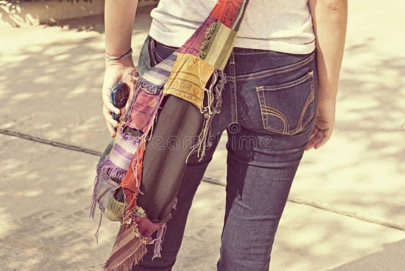 牛仔裤的青少年的女孩有手机的 免版税库存照片