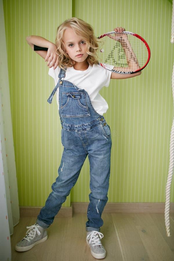 牛仔裤的年轻美丽的女孩穿衣与网球拍 免版税库存照片