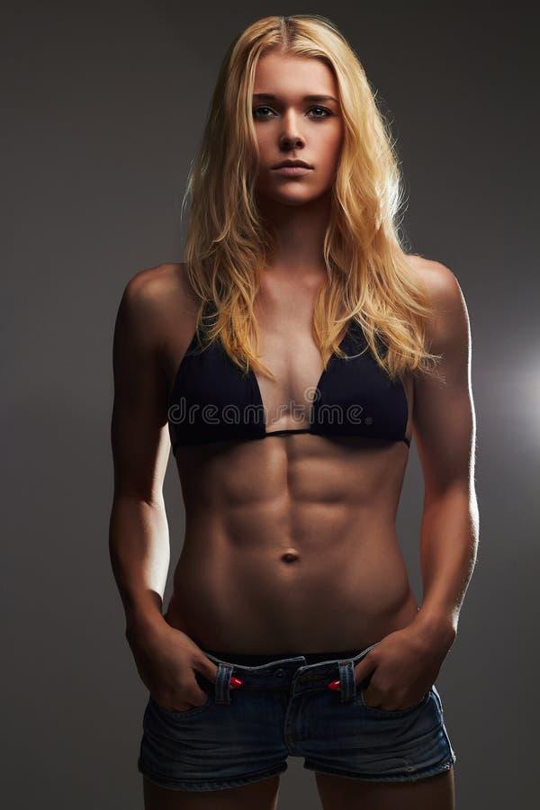 牛仔裤短裤的Exy美丽的运动女孩 肌肉健身少妇 图库摄影