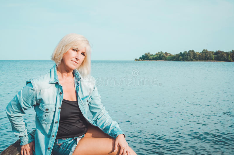 牛仔裤衬衣的白肤金发的中年妇女,坐一个海滩有蓝天背景,拷贝空间 画象有吸引力 免版税库存图片