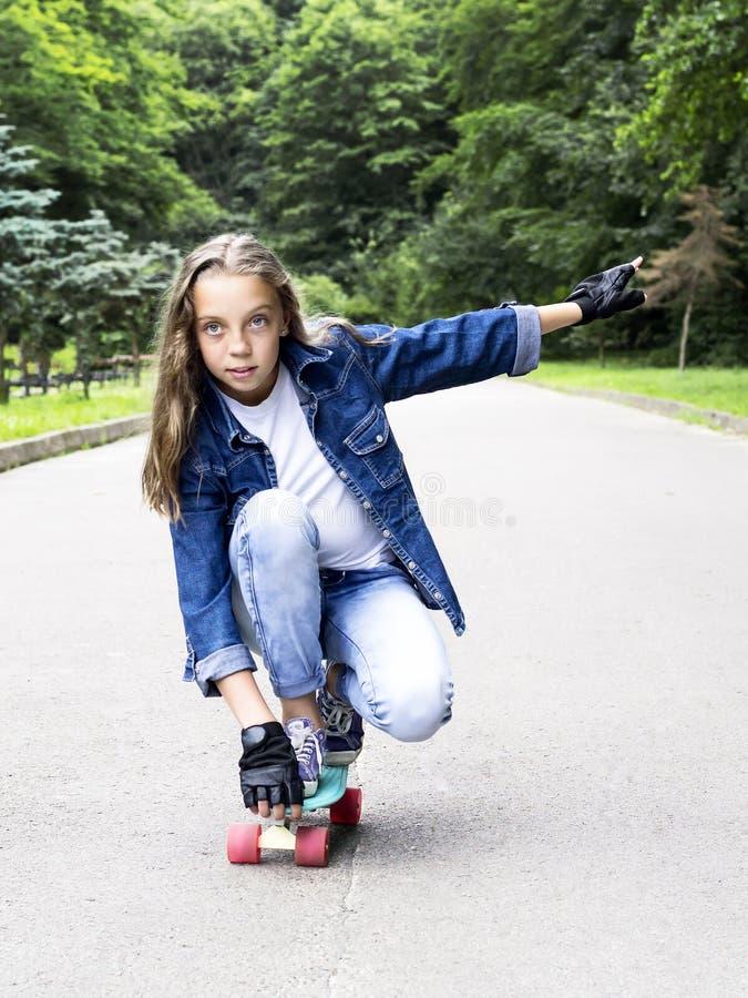牛仔裤衬衣的美丽的白肤金发的青少年的女孩,在滑板在公园 免版税库存照片