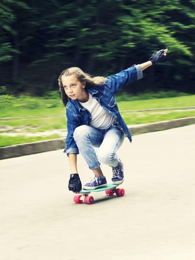 牛仔裤衬衣的美丽的白肤金发的青少年的女孩,在滑板在公园 库存照片