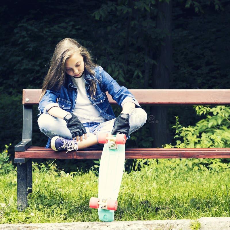 牛仔裤衬衣的美丽的白肤金发的青少年的女孩,坐与背包和滑板的长凳在公园 免版税库存图片